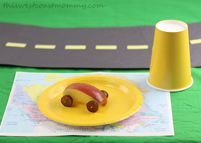 Road trip theme place setting. Create a play road from construction paper, add matching yellow paper cups and plates, and use recycled map book pages to make placemats.