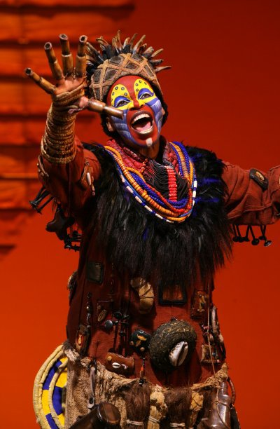 "Tshidi Manye as ""Rafiki"" in the opening number ""The Circle of Life"" from THE LION KING National Tour. ©Disney. Photo Credit: Joan Marcus."